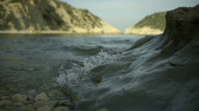 slo mo sea swell next to smooth rock - erodiert stock-videos und b-roll-filmmaterial