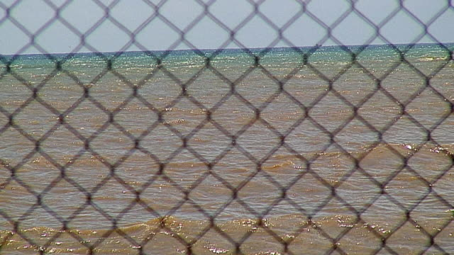 ws sea through chainlink fence, tangalla, sri lanka - chainlink fence stock videos and b-roll footage