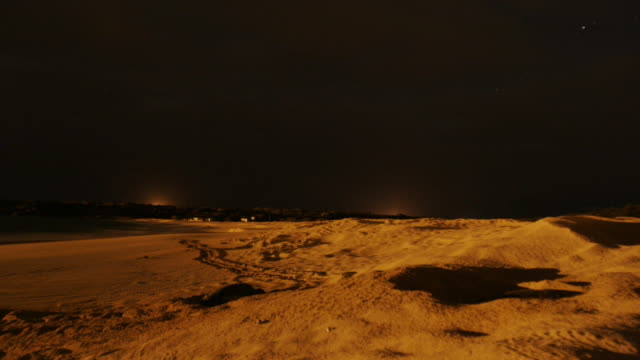 sea turtles deposit their eggs in shallow holes along a sandy beach at night, then return to the sea. available in hd. - scavare video stock e b–roll