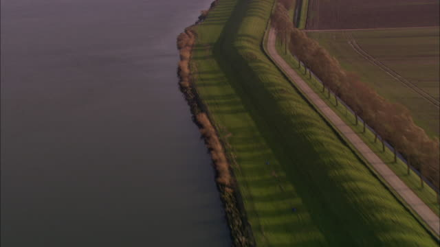 a sea wall surrounds a dutch city. - levee stock videos & royalty-free footage