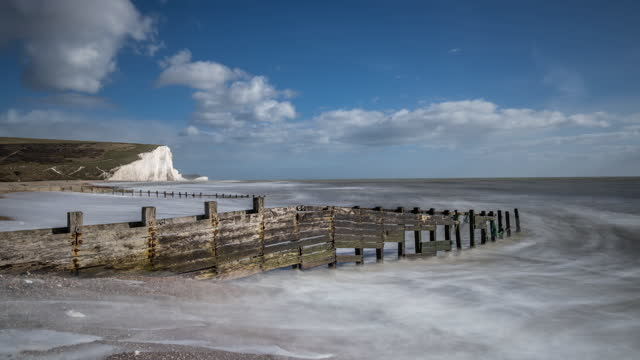 sea washes onto pebble beach by dilapidated wooden groyne, seven sister's white chalk cliff behind, blue sky and rapidly moving clouds above. - run down stock videos & royalty-free footage