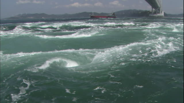 Sea water flow forms whirlpools beneath the Onaruto Bridge spanning the Naruto Strait in Japan.