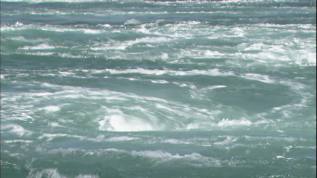 vídeos de stock e filmes b-roll de sea water swirls into a huge whirlpool in the naruto strait in japan. - espiral