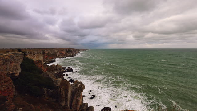 sea wave landscape crashing on rock coast with dark clouds - cliff dwelling stock videos & royalty-free footage
