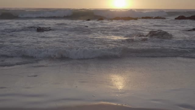 sea waves rushing at beach during sunset - riva dell'acqua video stock e b–roll