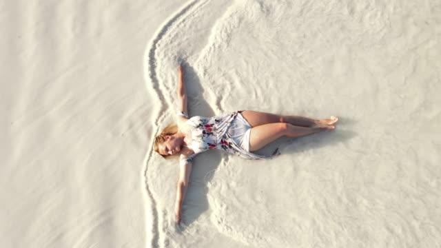 aerial sea waves splashing over a joyful woman lying on the beach - sundress stock videos & royalty-free footage