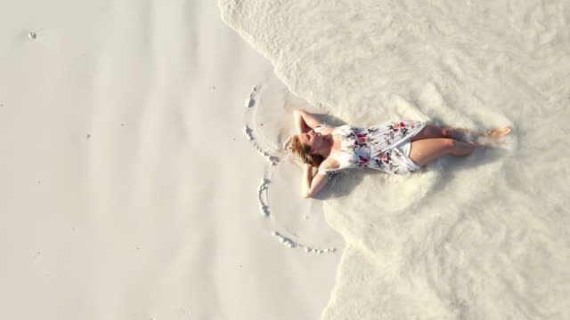 aerial sea waves splashing over a woman in sundress lying on the beach - sundress stock videos & royalty-free footage