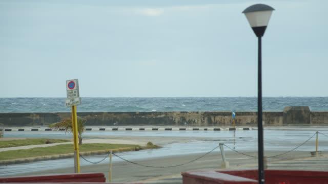 vídeos y material grabado en eventos de stock de sea waves surging onto the malecon coastal road in havana, cuba on a cloudy day - pared de cemento