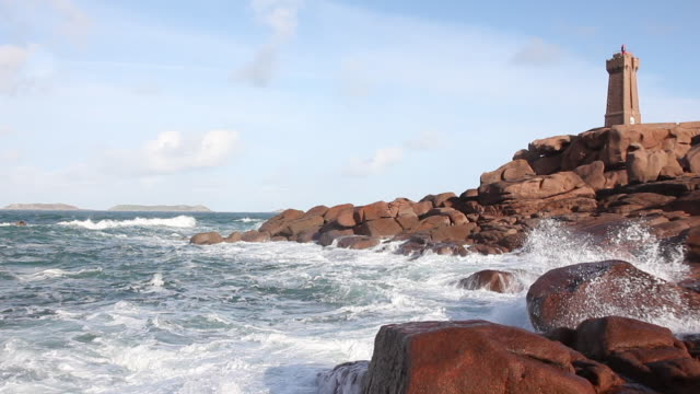 sea with rocks and a lighthouse - bretagna video stock e b–roll