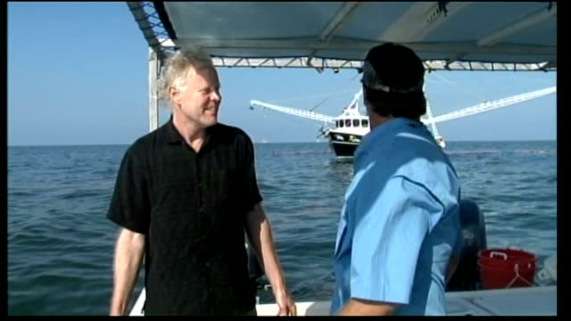 Seabirds flying over water and Steiner discussing environmental damage with other man on boat SOT