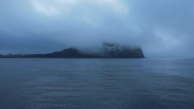 vídeos de stock, filmes e b-roll de seacape of seongsan ilchulbong tuff cone full of sea fog and cloud in seogwipo city / jeju-do, south korea - superfície de água