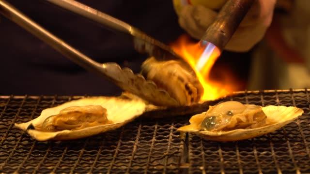 vídeos y material grabado en eventos de stock de vieiras de marisco a la plancha en el mercado de pescado en japón - foco difuso
