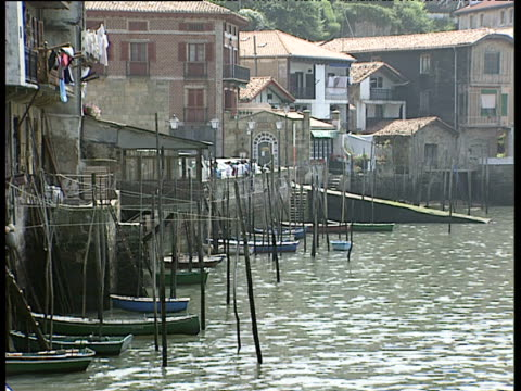 Seafront buildings with small boats moored against pilings San Sebastian