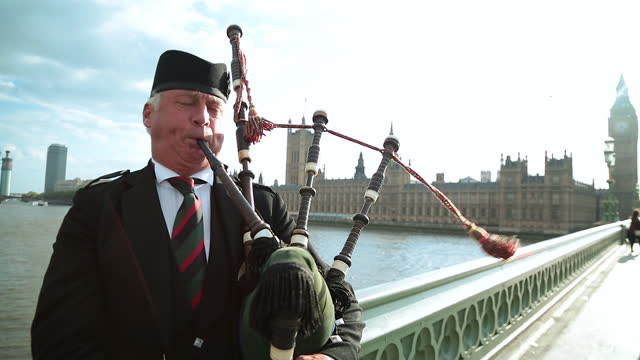 seagull flies overhead as man plays bagpipes on westminster bridge overlooking the palace of westminster. - house of commons stock videos & royalty-free footage