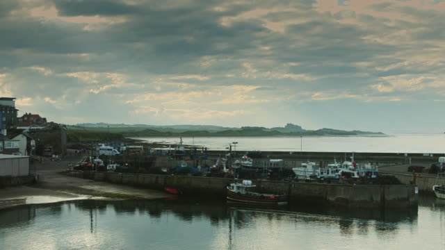 seahouses harbour with bamburgh castle - northumberland video stock e b–roll