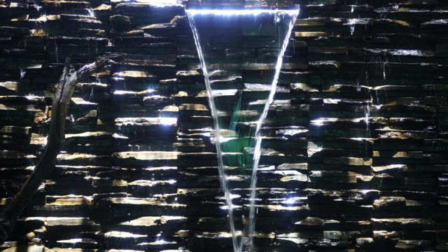緑の苔で暗い岩の顔に沿って下る水のシームレスなループ映像。自然と環境のための背景装飾ビデオやイラスト。 - にじみ出す点の映像素材/bロール
