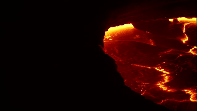 Seams of molten lava bubble and split in a volcano crater. Available in HD.