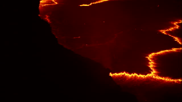 Seams of molten lava cross a volcano crater. Available in HD.