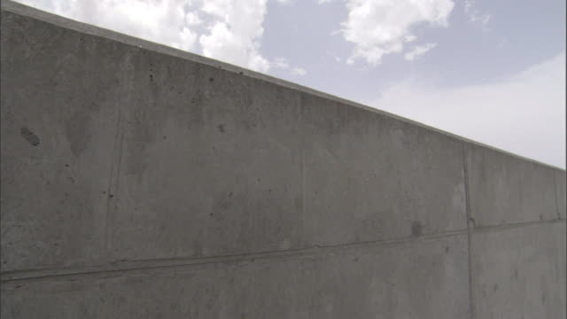 Seams show on the concrete wall of a levee.