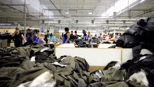 a seamstress attaches a canada goose inc patch to a piece of fabric on the production line at the company's manufacturing facility in toronto ontario... - textile patch stock videos & royalty-free footage