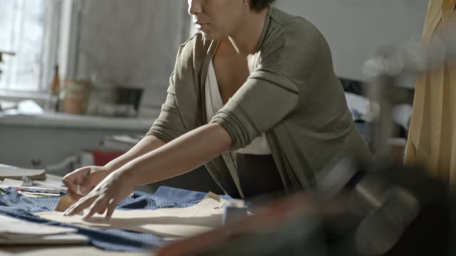 Seamstress outlining pattern on fabric in sewing workshop