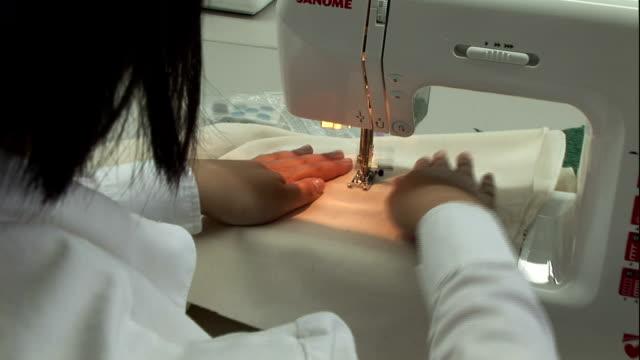 vidéos et rushes de a seamstress runs fabric through a sewing machine. - machinerie