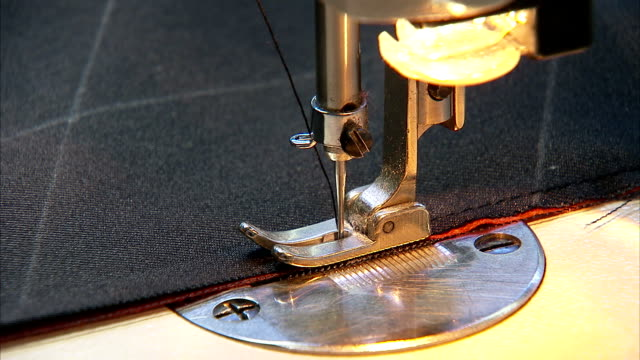a seamstress sews fabric with a machine. - sewing machine stock videos & royalty-free footage