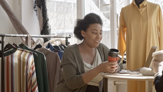 seamstresses chatting and drinking coffee in sewing workshop - パタンナー点の映像素材/bロール