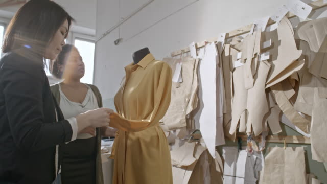 seamstresses checking seams on dress in workshop - fashion designer stock videos and b-roll footage