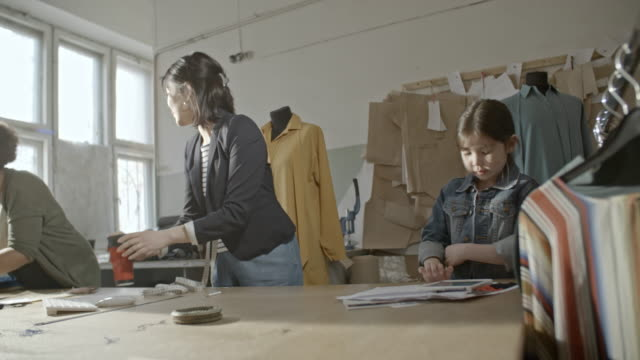 seamstresses cleaning up sewing workshop - 人工物点の映像素材/bロール