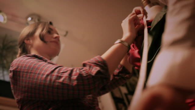 ms seamstresses draping and measuring fabric on dress form / new york city, new york, usa - トルソー点の映像素材/bロール