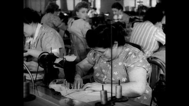 Seamstresses working at sewing machines MS Woman sewing w/ machine MS Woman hand sewing buttons LS Men pressing w/ irons in press room MS Man...
