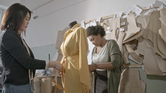 Seamstresses working on yellow dress in workshop