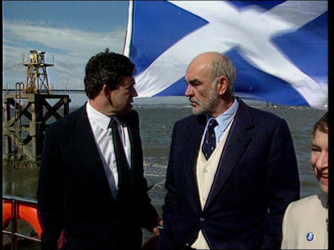 scotland firth of forth la gv forth bridge pan to sean connery standing on boat next gordon brown mp as st andrew's flag flies behing them edinburgh... - firth of forth bildbanksvideor och videomaterial från bakom kulisserna