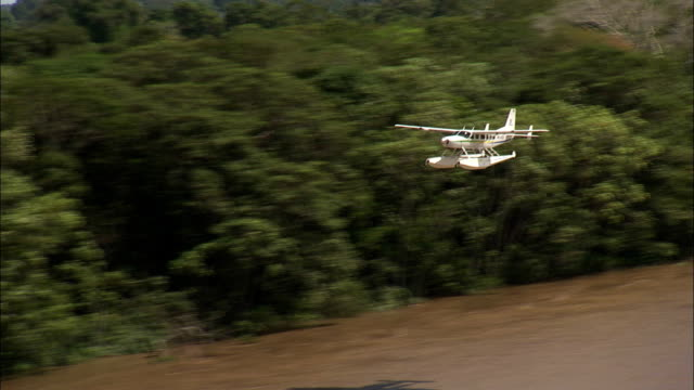 A seaplane flies low over the Amazon River. Available in HD.