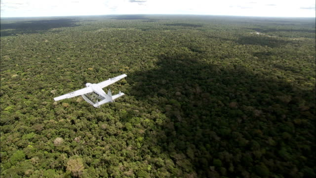 a seaplane flies over the amazon rainforest. available in hd. - rainforest stock videos & royalty-free footage