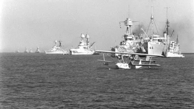 a seaplane floats near warships as a launch sails past. - 水上飛行機点の映像素材/bロール