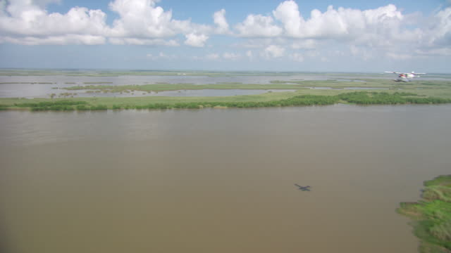 aerial ws seaplane flying over delta gulf / new orleans, louisiana, united states - 水上飛行機点の映像素材/bロール