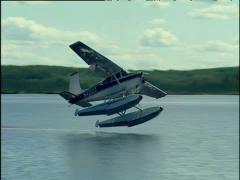 seaplane skis along water then rises into the air and flies into the horizon. - 水上飛行機点の映像素材/bロール