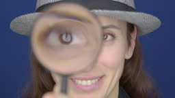 Search. A young woman with a magnifying glass searching, investigates and studies.