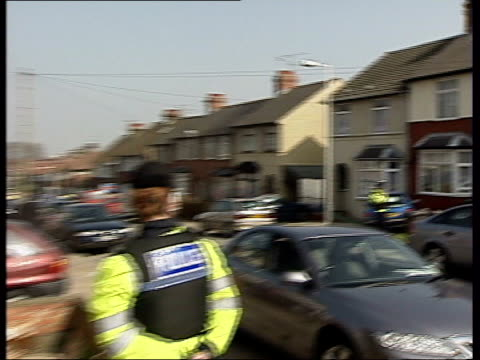 Luton EXT LS police officers in bullet proof vests on duty outside house raided by police searching for terror suspects PAN to police outside another...