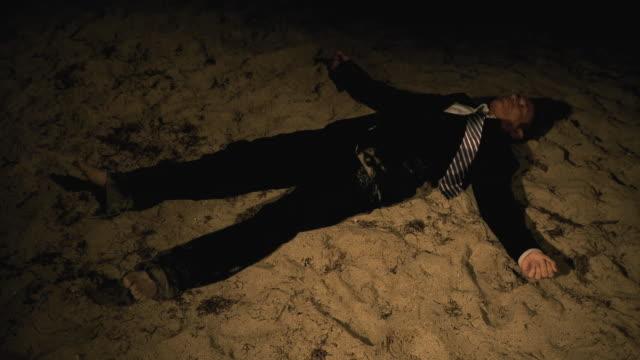 MS Search light on man lying unconscious on sand, South Beach, Florida, USA