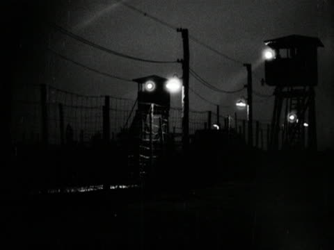Search lights scan the perimeter fence of a concentration/prison camp