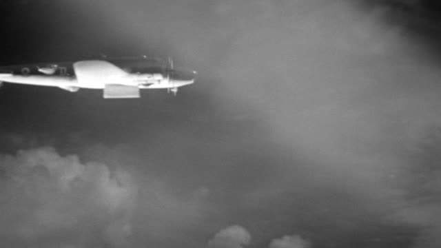 ms ts search lights sweep sky as b17 airplane flies through clouds (miniature) - tracking shot stock videos & royalty-free footage
