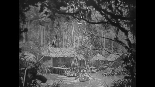 1925 search party in small kayaks leave grass huts in tropics - 草葺小屋点の映像素材/bロール