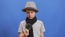 Search with a magnifier. A little boy search something with a magnifier.
