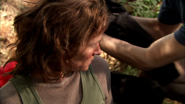 a searcher comforts and covers a lost hiker just discovered in a wilderness area. - befreiung stock-videos und b-roll-filmmaterial