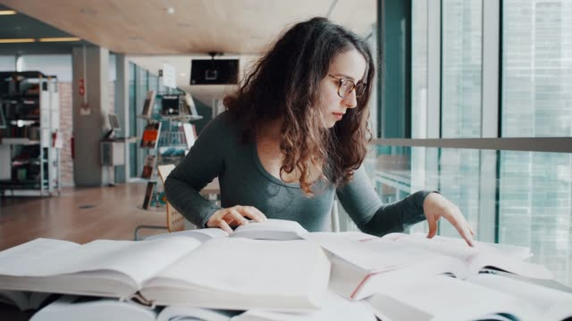 searching for the right information from a lot of books - studentessa video stock e b–roll