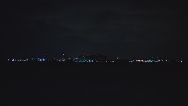 a searchlight illuminates a cloudy sky above miami. - horizon stock videos & royalty-free footage