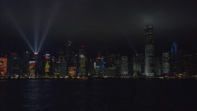 Searchlights illuminate the sky from atop a skyscraper.